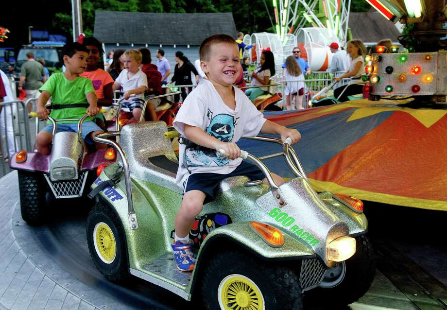 Corey Oppenheimer, 5, seems to enjoy a ride during the St. Catherine of Siena Church carnival in Greenwich, Conn., on August 15, 2014. Photo: Lindsay Perry / Stamford Advocate
