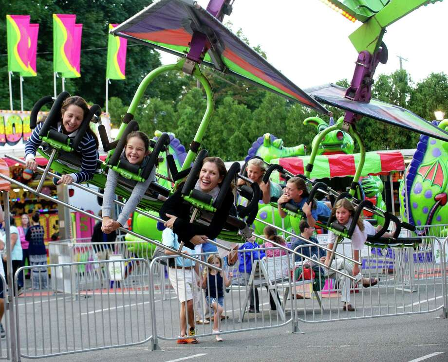 Fairgoers enjoy rides during the St. Catherine of Siena Church carnival in Greenwich, Conn., on August 15, 2014. Photo: Lindsay Perry / Stamford Advocate
