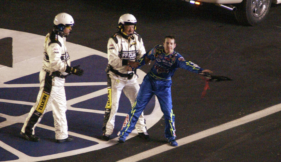FILE - In this May 28, 2006, file photo, driver Kyle Busch is restrained by a NASCAR official as he throws his neck brace at the passing car of driver Casey Mears (not shown) after Busch crashed during the NASCAR Nextel Cup Series Coca-Cola 600 auto race at the Lowe's Motor Speedway, in Concord, N.C. NASCAR added a rule Friday, Aug. 15, 2014,  ordering drivers to not approach the track or moving cars after accidents.  (AP Photo/Bob Jordan, File) ORG XMIT: NY160 Photo: BOB JORDAN / AP