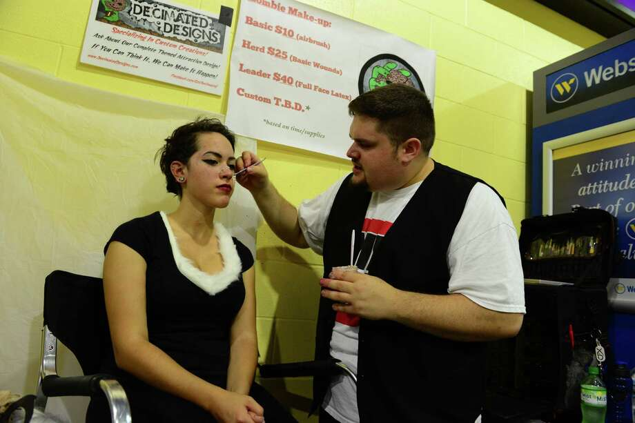 Alissa Espinelo, of Seymour, gets the zombie makeup treatment from artist Kyle Pasciutti, during Connecticut ComiCONN at the Webster Bank Arena in downtown Bridgeport, Conn. on Friday, August 15, 2014. ComiCONN continues through Sunday. Photo: Christian Abraham / Connecticut Post