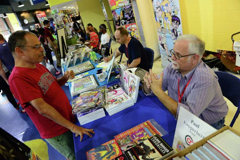 Writer Paul Kupperberg, right, chats with fan David Frank, of New haven, during Connecticut ComiCONN at the Webster Bank Arena in downtown Bridgeport, Conn. on Friday, August 15, 2014. ComiCONN continues through Sunday. Photo: Christian Abraham / Connecticut Post