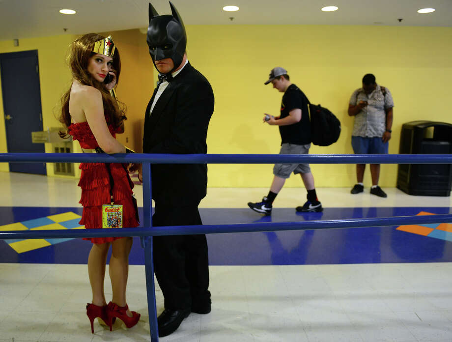 Kuno Yuro, of Boston, is dressed up as Wonder Woman, and her friend Matches Malone, also from Boston, is dressed up as Batman, during Connecticut ComiCONN at the Webster Bank Arena in downtown Bridgeport, Conn. on Friday, August 15, 2014. ComiCONN continues through Sunday. Photo: Christian Abraham / Connecticut Post