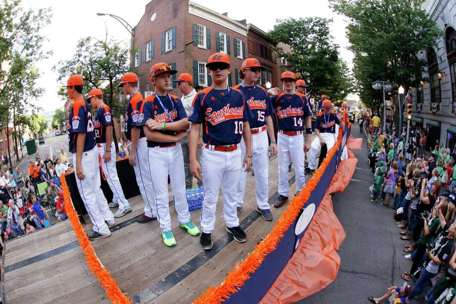 Members of the Pearland East Little League team from Pearland, Texas ride in the Little League Grand Slam Parade as it makes its way through downtown Williamsport, Pa., Wednesday, Aug. 13, 2014. The Little League World Series tournament begins Thursday, August 14, in South Williamsport, Pa..  (AP Photo/Gene J. Puskar) Photo: Gene J. Puskar, Associated Press / AP