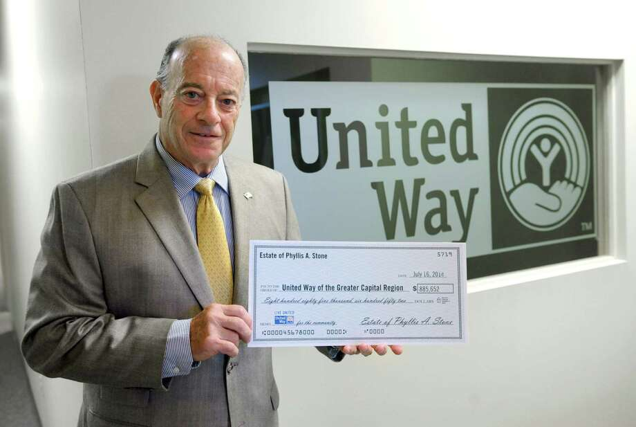 Immediate past board chair John Kearney holds a mock check of made out to the United Way of the Greater Capital Region from the estate of Phyllis Stone at the organization's office on Wednesday, Aug. 13, 2014 in Albany, N.Y. Phyllis Stone was a low-key and an unknown millionaire who died at 91 last year and gave $888,652 to the United Way of the Greater Capital Region, its largest gift ever. (Lori Van Buren / Times Union) Photo: Lori Van Buren / 00028167A