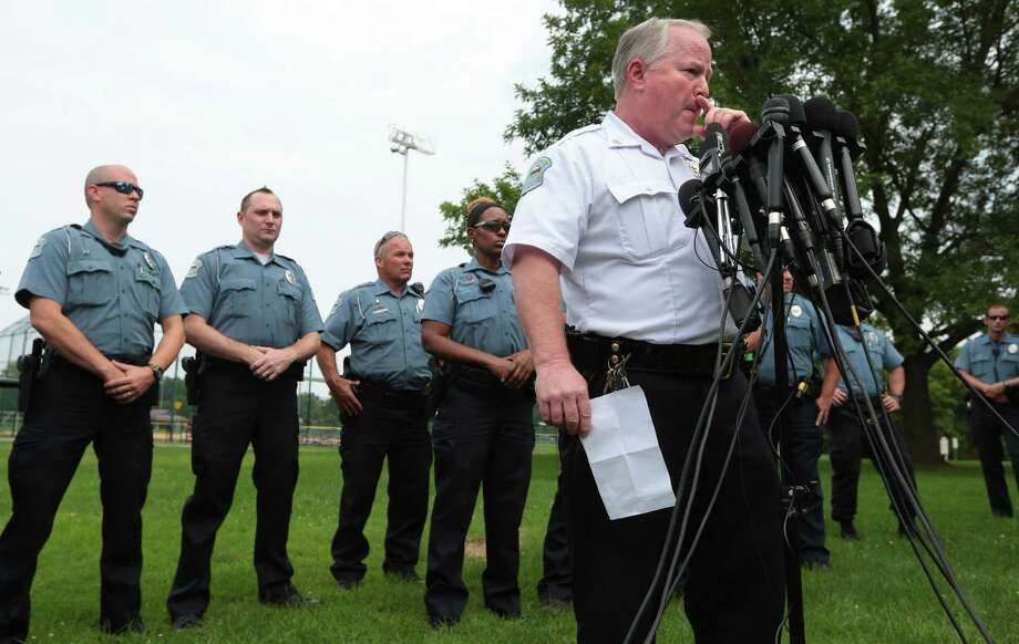 Ferguson Police Chief Tom Jackson is surrounded by his officers as he answers questions at a news conference in Forestwood Park on Friday, Aug. 15, 2014.  Jackson took questions in the quiet park after earlier identifying Darren Wilson as the officer who shot Michael Brown. (AP Photo/St. Louis Post-Dispatch, Robert Cohen) ORG XMIT: MOSTP103 Photo: Robert Cohen / St. Louis Post-Dispatch