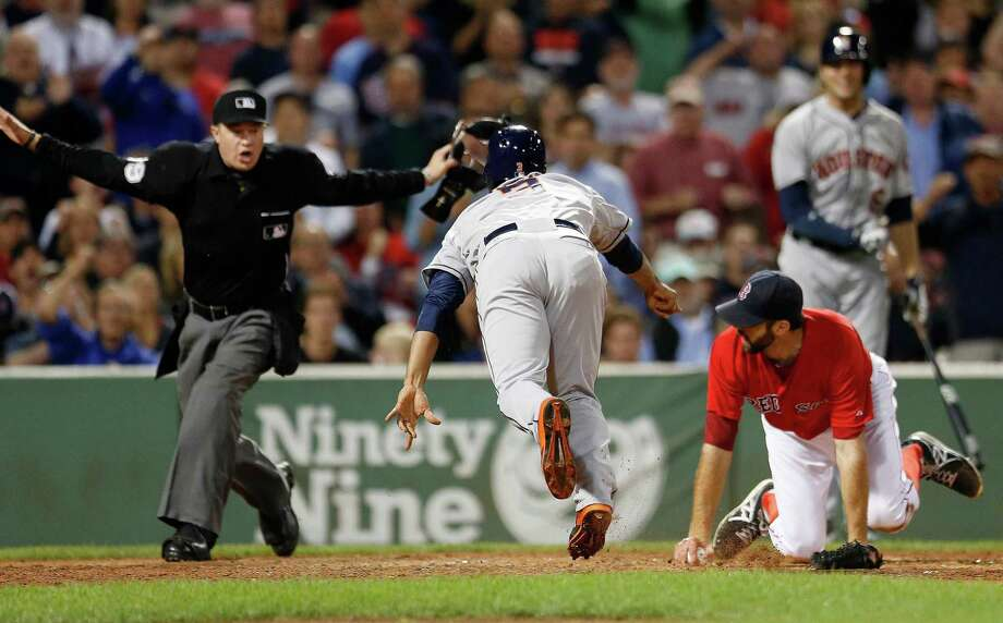 The Astros' Gregorio Petit (3) and Red Sox pitcher Burke Badenhop, lower right, look up when plate umpire Cory Blaser makes the call as Petit scores from second on a fielder's choice in the eighth inning Friday. Photo: Michael Dwyer, STF / AP