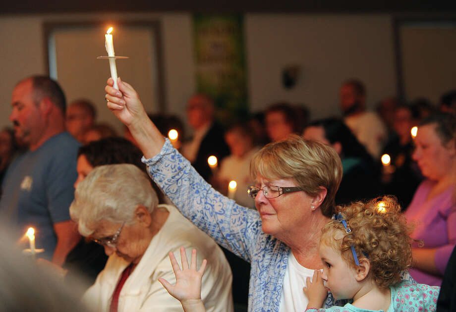 Lillian LaRose, Heuvelton, holds up a candle on Thursday, Aug. 14, 2014 during a candlelight vigil at the Cornerstone Wesleyan Church in Heuvelton for Fannie Miller, 12, and her sister Delila Miller, 6, who were still missing after being abducted Wednesday night at a farm stand near their home. (AP Photo/The Watertown Daily Times, Jason Hunter) ORG XMIT: NYWAT102 Photo: Jason Hunter / The Watertown Daily Times