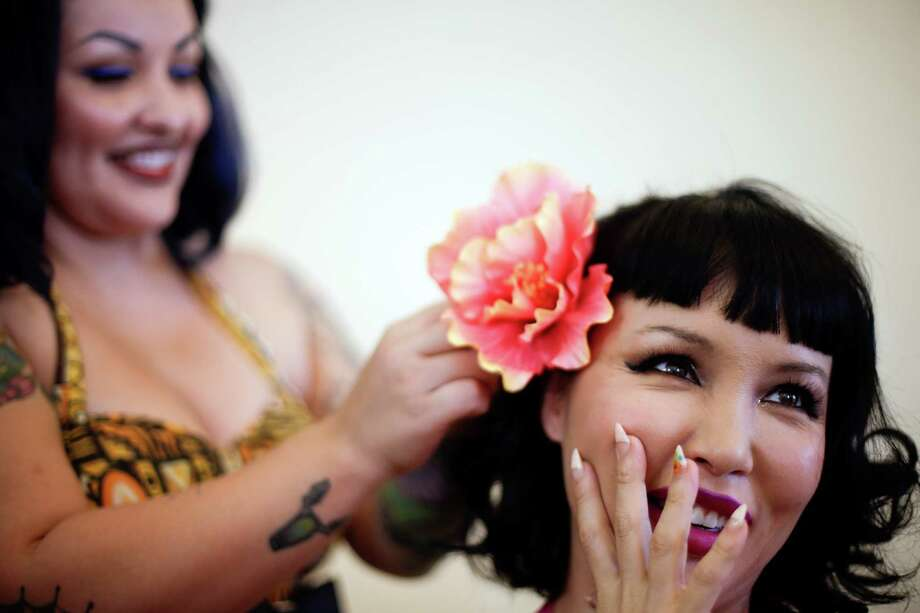 Masuimi Max, right, laughs as she gets a hairstyle by Jennifer Corona during the Tiki Oasis event Friday, Aug. 15, 2014, in San Diego. Hundreds of tiki culture aficionados, clad in tropical colors, gathered Friday for a weekend-long celebration that revels in the movements from the 1950s and 1960s.  Photo: Gregory Bull, Associated Press / AP