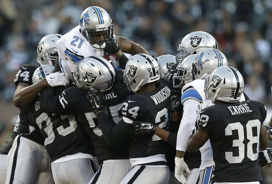Running back Reggie Bush (21) meets a wall of Raiders defenders, who limited the Lions to roughly 2 yards per carry. Photo: Ben Margot, Associated Press
