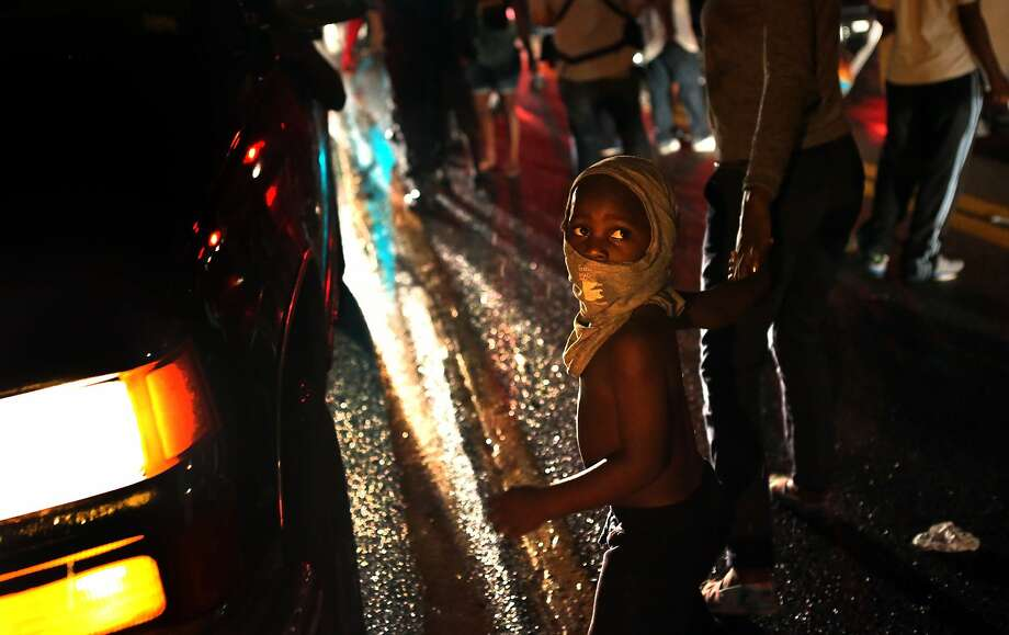 Isaiah King Ivy, 3, makes his shirt a mask as he participates in demonstrations with his north St. Louis County family on West Florissant Avenue in Ferguson on Friday, Aug. 15, 2014.  (AP Photo/St. Louis Post-Dispatch, Robert Cohen) Photo: Robert Cohen, Associated Press