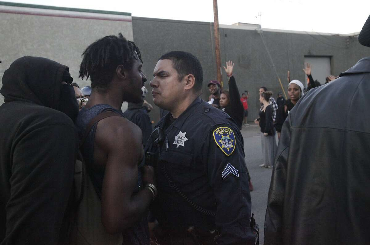 A police officer and a protester have a tense moment before a scuffle breaks out between a different protester and police officers near the port during an