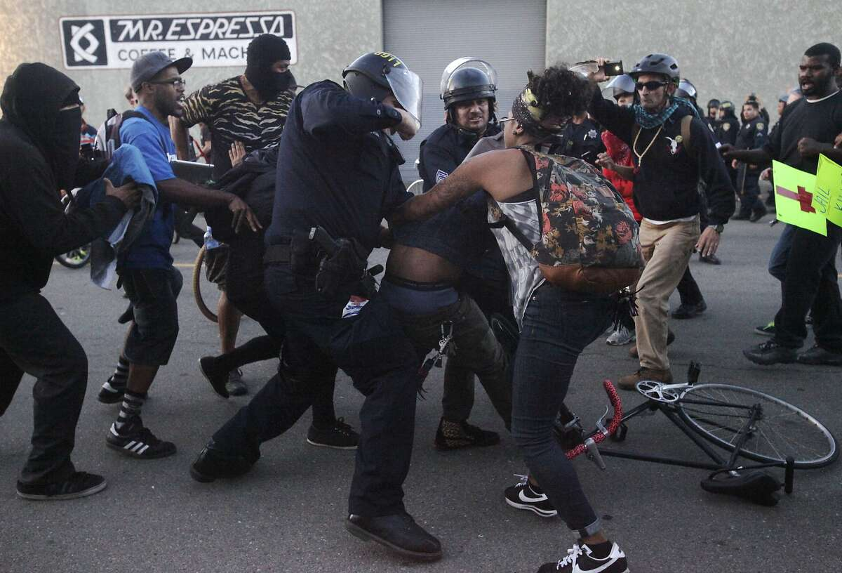 A woman tries to pull a protester from police officers after a scuffle broke out between them during an