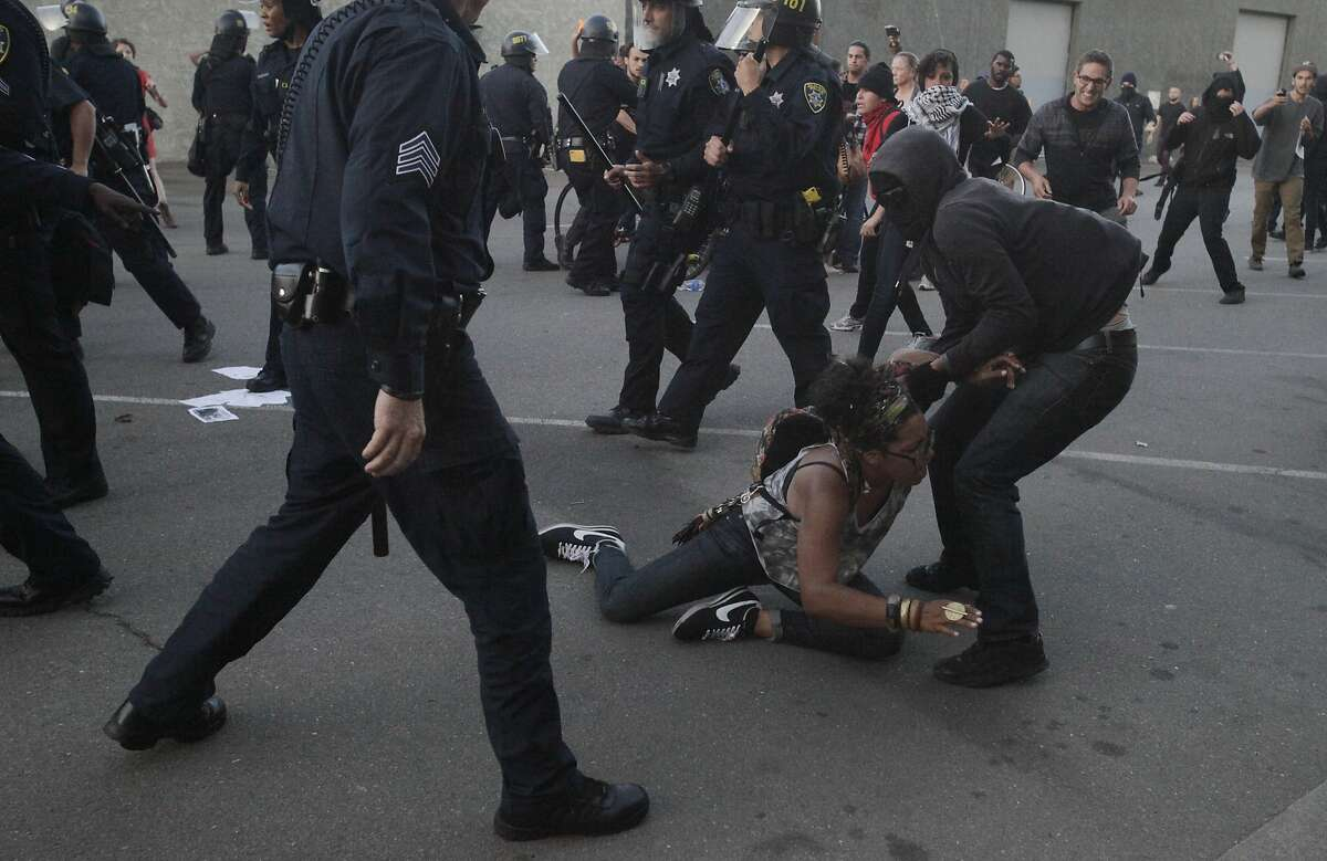 One protester helps a woman up after she was involved in a scuffle between police and a protester during an