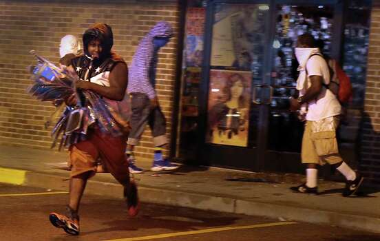 A looter escapes with items from Feel Beauty Supply on West Florissant Avenue in Ferguson early Saturday, Aug. 16, 2014, after protestors clashed with police. Photo: Robert Cohen, AP / St. Louis Post-Dispatch