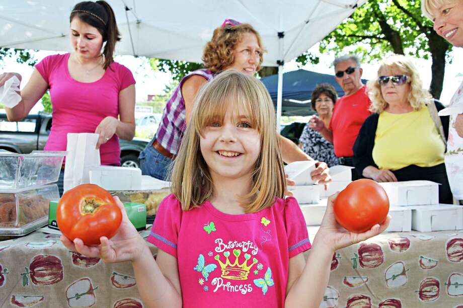 Four-year-old Morgan Starr of Rock City Falls with two perfect tomatoes she bought at the Ballston Spa Farmer's Market Thursday Aug. 16, 2012.  (John Carl D'Annibale / Times Union) Photo: John Carl D'Annibale