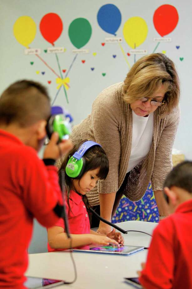 Leslie Ramirez, 5, gets help from teacher Lilian Davila during iPad exercises at Rusk Elementary School in Houston. According to the Texas Education Agency, only 9 percent of the state's schools fell short of targets or require improvement. Photo: Mayra Beltran, Staff / © 2012 Houston Chronicle