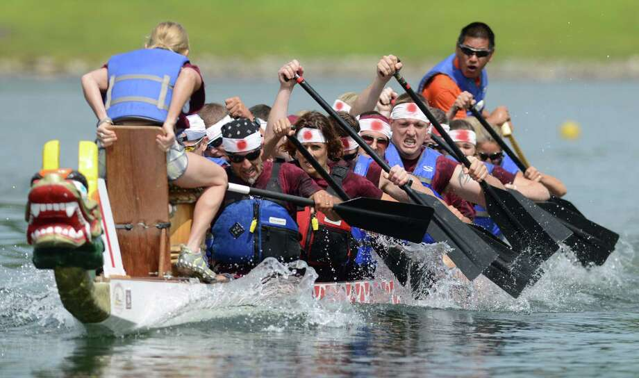Participants compete in a heat at the Sixth Annual Candlewood Lake Dragon Boat Race at Lynn Deming Park in New Milford, Conn. Saturday, Aug. 16, 2014.  Teams of 20 rowers and one drummer raced 46-foot-long boats with wooden carved dragons at the bow on a 200 meter course on Candlewood Lake.  Teams were made up of Candlewood Lake community residents, local businesses or just groups of friends wanting to compete.  There was also food, swimming, demonstrations and music by the UConn Taiko Japanese drum group to entertain participants in the Candlewood Lake Authority's largest fundraiser of the year. Photo: Tyler Sizemore / The News-Times