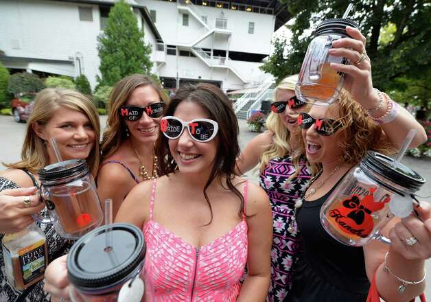 Bride-to-be Jeanine O'Connor of Schenectady, center is surrounded by her bridal party of Rachel Curtis, left Leann Thrane,second from left, Heather Robles, second from right and Kendra O'Connor, right during their bachelorette party at the Saratoga Race Course Saturday afternoon Aug. 16, 2014, in Saratoga Springs, N.Y.  An October 3rd wedding is planned.  (Skip Dickstein/Times Union)J Photo: SKIP DICKSTEIN