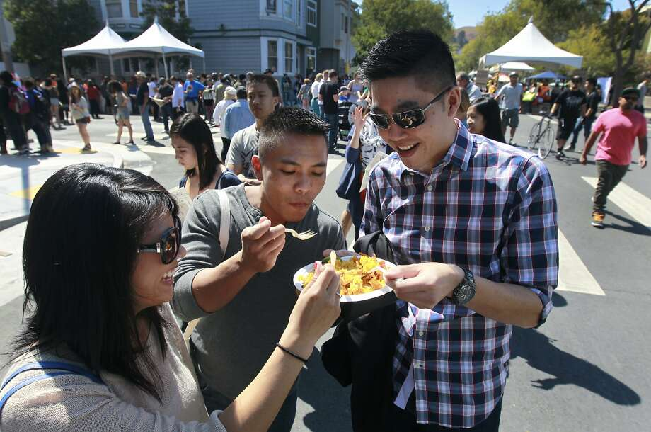 Erin Sarmiento (left), Keith Do and Henry Liu share a plate of food while they wait in line to order more at the sixth annual San Francisco Street Food Festival in the Mission. Photo: Paul Chinn, The Chronicle