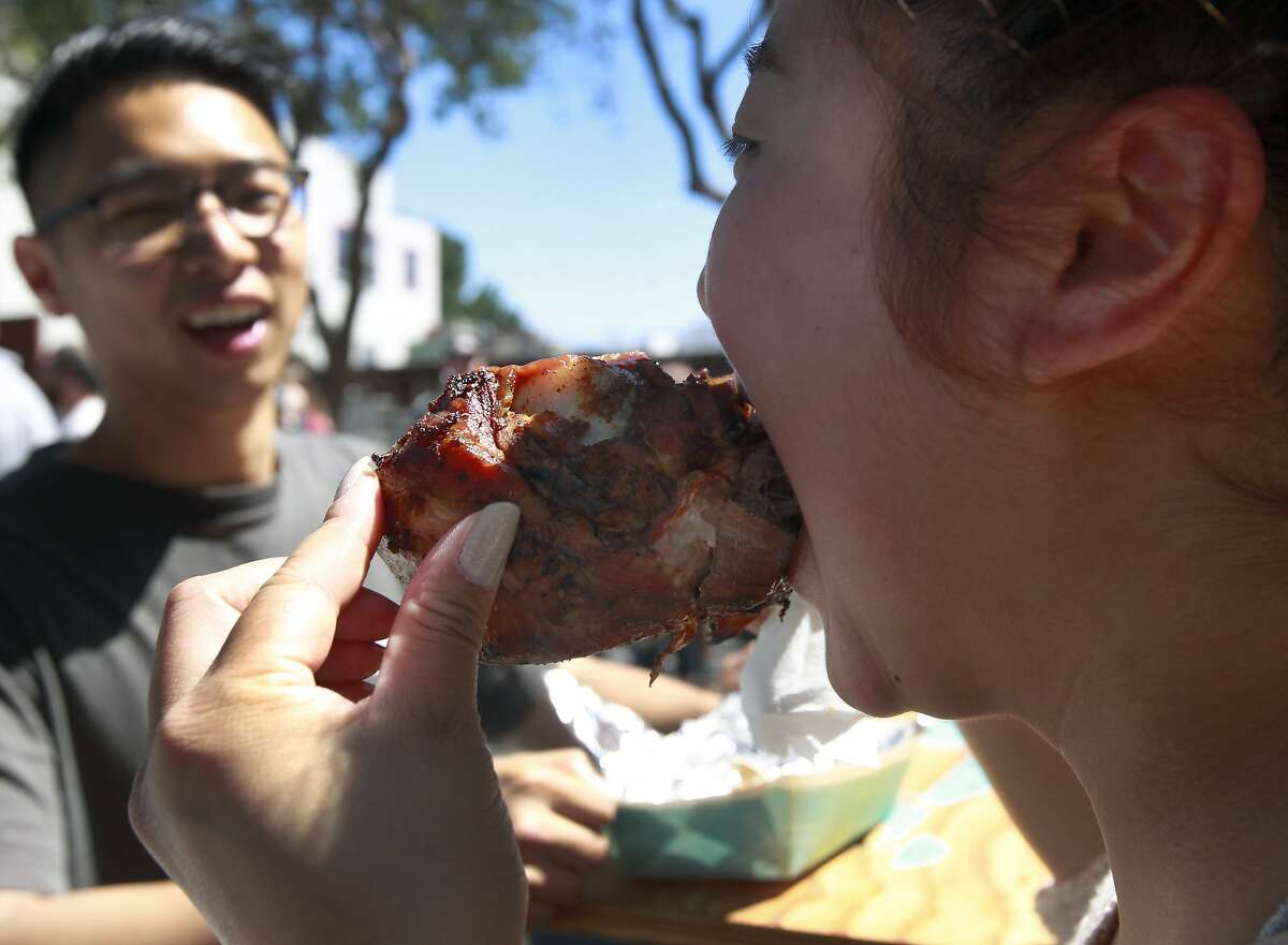 Tiffany Hoang shares a turkey leg from Zella's Soulful Kitchen with Jacky Lo (left) at the 6th annual San Francisco Street Food Festival on Folsom Street in San Francisco, Calif. on Saturday, Aug. 16, 2014. The six-block long gastronomic extravaganza, organized by small restaurant incubator La Cocina, has outgrown its current location and will likely need to find a larger venue if the event is staged again next year.