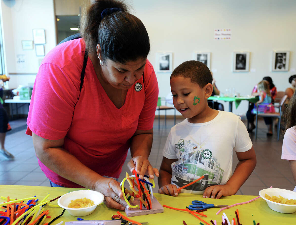 """Pamela Guidry works on a small sculpture with Jacob Guidry, 6, on Saturday morning. The Art Museum of Southeast Texas held one of its quarterly Family Art Days on Saturday, focusing on the theme of """"don't mess with Texas"""" and the use of recycled materials in creating art. Photo taken Saturday 8/16/14 Jake Daniels/@JakeD_in_SETX"""