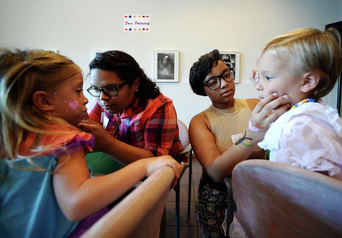 """Charlotte Oliphant, 5, far left, gets her face painted by Ana Landaverde, center left, as Yasmine Grogan, center right, paints the cheek of Emily Claire Cavett, 3, on Saturday morning. The Art Museum of Southeast Texas held one of its quarterly Family Art Days on Saturday, focusing on the theme of """"don't mess with Texas"""" and the use of recycled materials in creating art. Photo taken Saturday 8/16/14 Jake Daniels/@JakeD_in_SETX"""