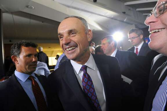 Major League Baseball Chief Operating Officer Rob Manfred, center, smiles after team owners elected him as the next commissioner of Major League Baseball during an owners quarterly meeting in Baltimore, Thursday, Aug. 14, 2014. (AP Photo/Steve Ruark)