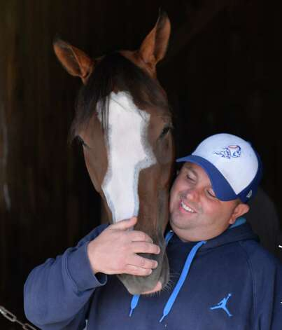 Assistant trainer Mike Tannuzzo gives some love to his favorite filly Hot Stones in the Bruce Levine Training barn Thursday, Aug. 7, 2014, at the Oklahoma Training Center in Saratoga Springs, N.Y. (Skip Dickstein/Times Union) Photo: SKIP DICKSTEIN