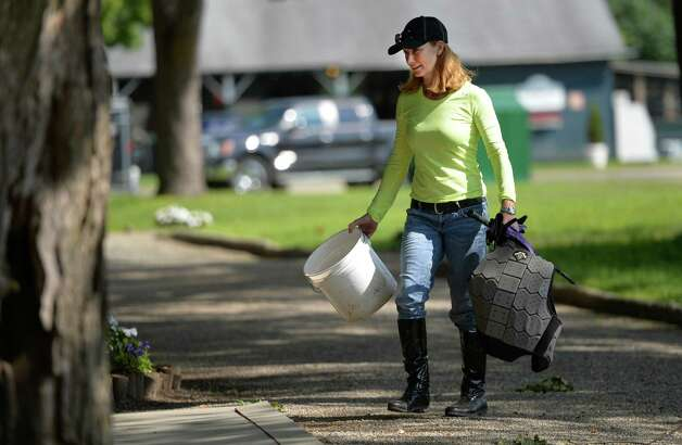 Exercise rider Maxine Correa cleans tack at the Nick Zito Training barn Thursday, Aug. 7, 2014, at the Oklahoma Training Center in Saratoga Springs, N.Y. (Skip Dickstein/Times Union) Photo: SKIP DICKSTEIN