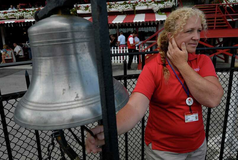 Bell ringer Jennifer Carlone rings the bell in the winner's circle Thursday, Aug. 7, 2014, at Sarato