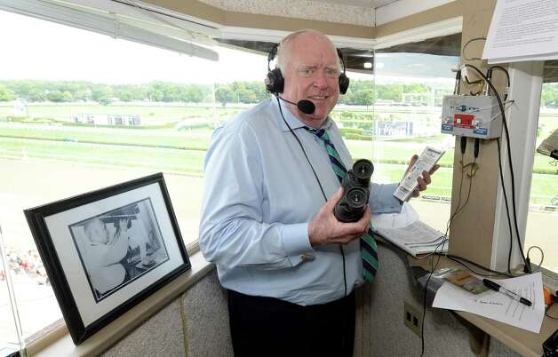 Retiring track announcer Tom Durkin prepares for a race Thursday, Aug. 7, 2014, at Saratoga Race Course in Saratoga Springs, N.Y. The photo in the booth with Durkin is former track announcer Fred Capossela. (Skip Dickstein/Times Union) Photo: SKIP DICKSTEIN