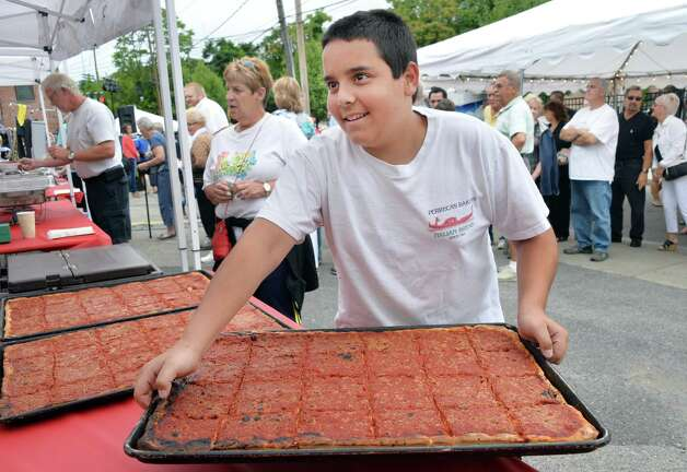 Nick Papa, 14, who's great grandparents founded the business, carries out a tray of pizza during Perreca's Bakery's 100th Birthday Block Party Saturday August 16, 2014, in Schenectady, NY.   (John Carl D'Annibale / Times Union) Photo: John Carl D'Annibale / 00028170A