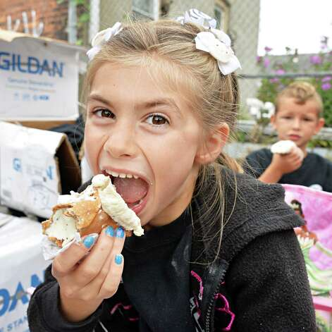 Six-year-old Marlene Cerone of Brunswick enjoys a cannoli during Perreca's Bakery's 100th Birthday Block Party Saturday August 16, 2014, in Schenectady, NY.   (John Carl D'Annibale / Times Union) Photo: John Carl D'Annibale / 00028170A