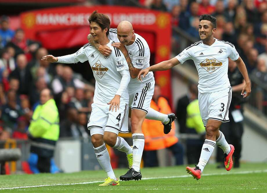 Ki Sung- Yeung celebrates scoring the opening goal with teammates Jonjo Shelvey and Neil Taylor as Swansea City made itself at home at Old Trafford. Photo: Alex Livesey, Getty Images