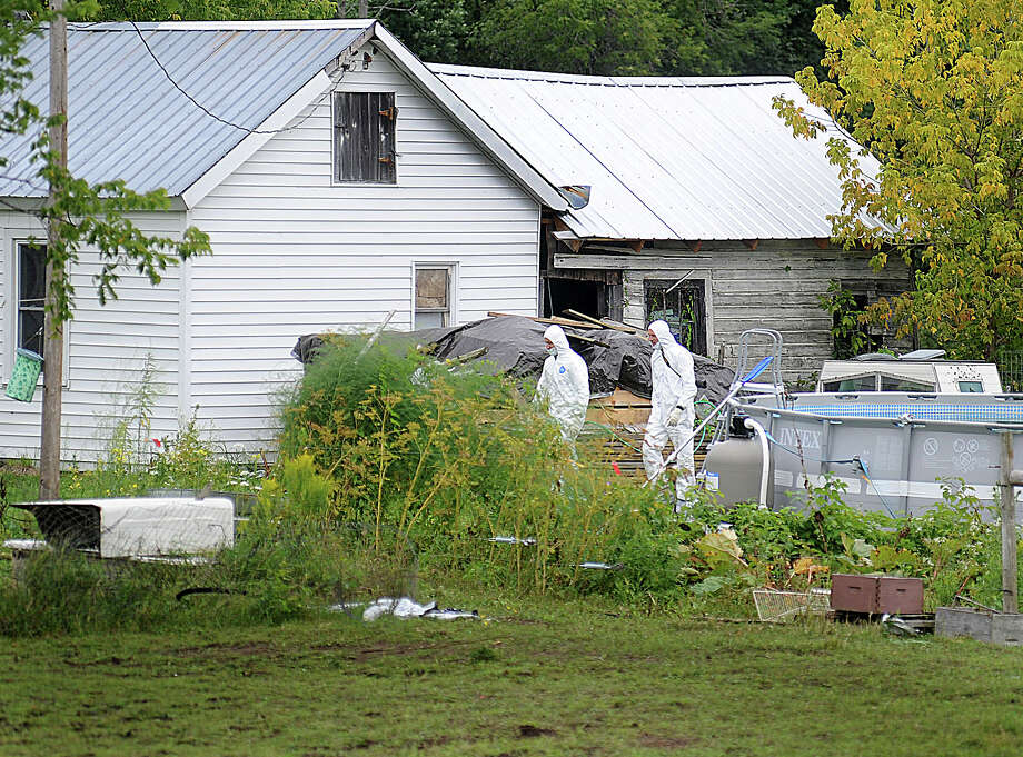 A pair of investigators walk on the property of Stephen Howells II and Nicole F. Vaisey, in Hermon, N.Y., Saturday, Aug. 16, 2014. Vaisey and Howells were arrested Friday on charges of first-degree kidnapping with the intent to physically harm or sexually abuse the victims. (AP Photo/Watertown Daily Times, Melanie Kimber Lago) MANDATORY CREDIT, SYRACUSE OUT ORG XMIT: NYWAT507 Photo: Melanie Kimbler-Lago / Watertown Daily Times