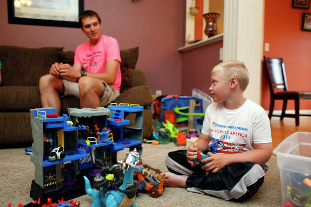 Shaun Evans, left, sits with his sons Shamus, inside the Evans residence on Tuesday, August 12, 2014 in East Galway, N.Y.  Shaun recently ran in a marathon with his son Shamus, who has Cerebral Palsy.  (Tom Brenner/ Special to the Times Union) Photo: Tom Brenner / ©Tom Brenner/ Albany Times Union