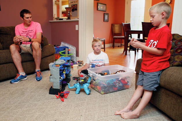 Shaun Evans, left, sits with his sons Shamus, center, and Simon, right,  inside the Evans residence on Tuesday, Aug. 12, 2014, in East Galway, N.Y.  Shaun recently ran in a marathon with his son Shamus, who has Cerebral Palsy.  (Tom Brenner/ Special to the Times Union) Photo: Tom Brenner / ©Tom Brenner/ Albany Times Union