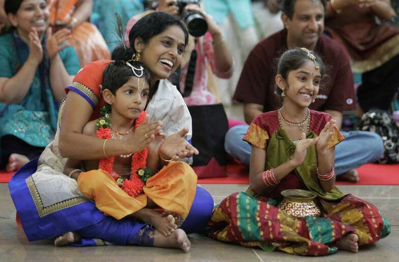 Sujatha Konaragiri with her son, Saketha, 4, and daughter Srividya, 7, applaud for the winners of the children's costume contest during the Krishna Janamashtami activities Saturday in The Woodlands.