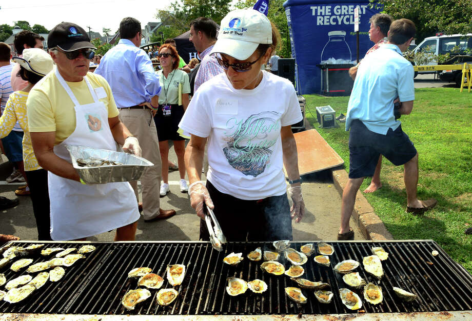 Marian Rossi grills oysters during the 40th Annual Milford Oyster Festival in downtown Milford, Conn. on Saturday, August 16, 2014. Photo: Christian Abraham / Connecticut Post