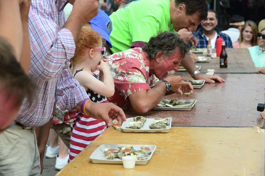 Several people including Milford Mayor Ben Blake take part in the oyster eating contest on Oyster Stage during the 40th Annual Milford Oyster Festival in downtown Milford, Conn. on Saturday, August 16, 2014. Photo: Christian Abraham / Connecticut Post