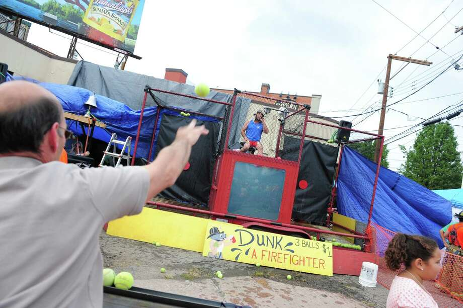 Milford firefighter Bernie Begley makes fun of the crowd as they try to dunk him, during the 40th Annual Milford Oyster Festival in downtown Milford, Conn. on Saturday, August 16, 2014.nn. on Saturday, August 16, 2014. Photo: Christian Abraham / Connecticut Post