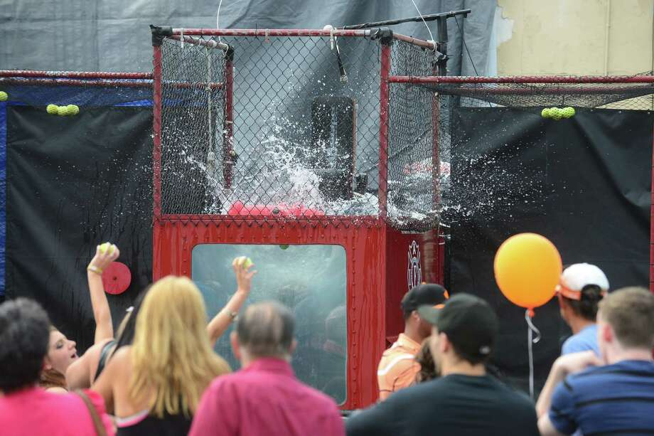Milford firefighter Bernie Begley makes fun of the crowd as they try to dunk him, during the 40th Annual Milford Oyster Festival in downtown Milford, Conn. on Saturday, August 16, 2014. Photo: Christian Abraham / Connecticut Post