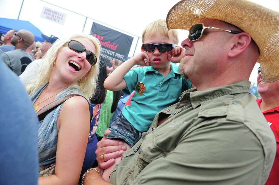 Three year old Alexander Ford, of Shelton, blocks his ears as Bret Michaels performs, during 40th Annual Milford Oyster Festival in downtown Milford, Conn. on Saturday, August 16, 2014. With him are his parents Valerie and Scott. Photo: Christian Abraham / Connecticut Post