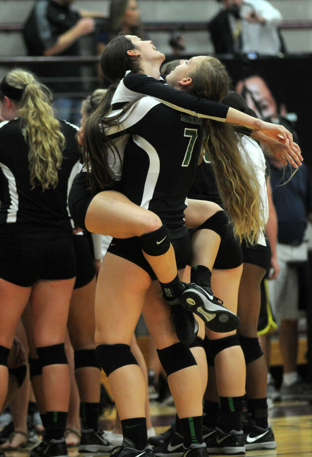 Southlake Carroll senior Libero Mykah Wilson, left, gets a victory ride in the arms of teammate and senior outside hitter Madison Drescher after the Dragon's two-set win over San Antonio O'Connor in the championship game of the 2014 Texas Volleyball Invitational at the Pearland High School Searcy Center on Saturday. Photo: Jerry Baker, For The Chronicle