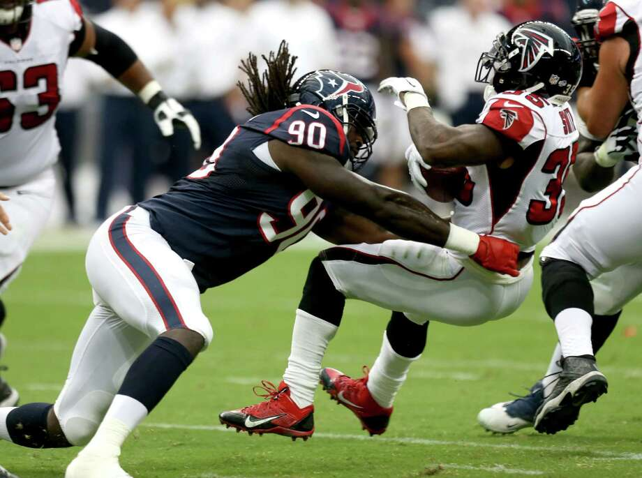 Jadeveon Clowney (90) gave the Texans more reason to believe they chose wisely with the No. 1 overall pick in the draft on this crowd-pleasing hit of Falcons running back Antone Smith in the first quarter of their 32-7 win Saturday night at NRG Stadium. Photo: Brett Coomer, Staff / © 2014  Houston Chronicle