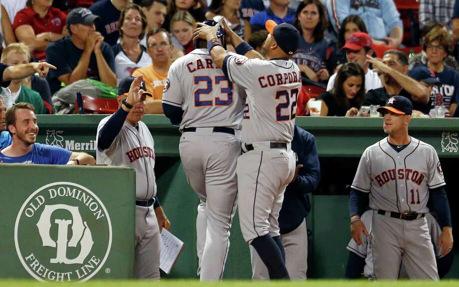 The Astros' Chris Carter (23) gets a celebratory assist from Carlos Corporan after hitting his 29th home run of the season in the fourth inning at Boston. Photo: Michael Dwyer, STF / AP