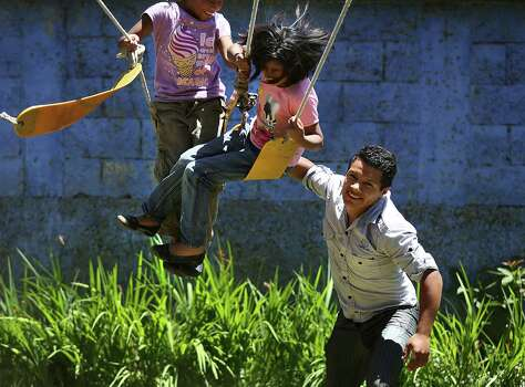 Juan, not his real name, right, pushes two orphan girls on a swing at Casa Rosa de Amor in San Lucas, Guatemala.  Once an orphan also, Juan now performs volunteer work for orphanages in the Antigua area in Guatemala.  Wednesday, July 23, 2014. Photo: Bob Owen, San Antonio Express-News / ©2013 San Antonio Express-News