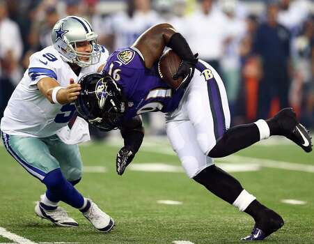 Tony Romo (left) tries to tackle Courtney Upshaw as the linebacker returns his fumble for a 26-yard first-half TD. Romo threw for 80 yards and a TD in his preseason debut. Photo: Ronald Martinez / Getty Images / 2014 Getty Images