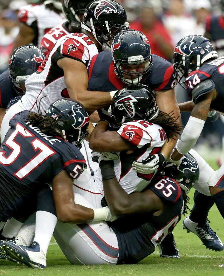 Texans linebackers Jason Ankrah (center) and Justin Tuggle (left) stop Falcons RB Jacquizz Rodgers. Photo: Brett Coomer, Houston Chronicle / © 2014  Houston Chronicle