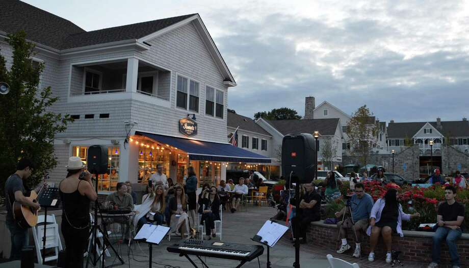 Musicians entertain the crowd Friday evening outside the Saugatuck Sweets shop in the new Saugatuck Center. Photo: Jarret Liotta / Westport News
